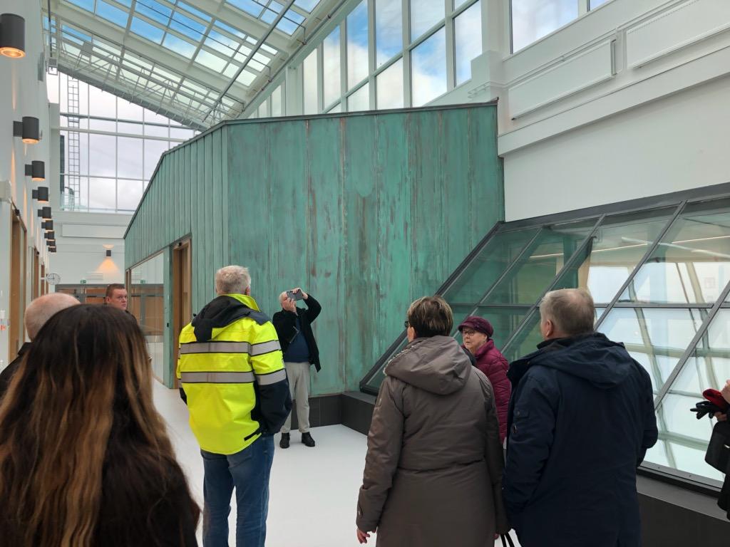 Ihmisiä aulatilassa, jossa lasinen katto.