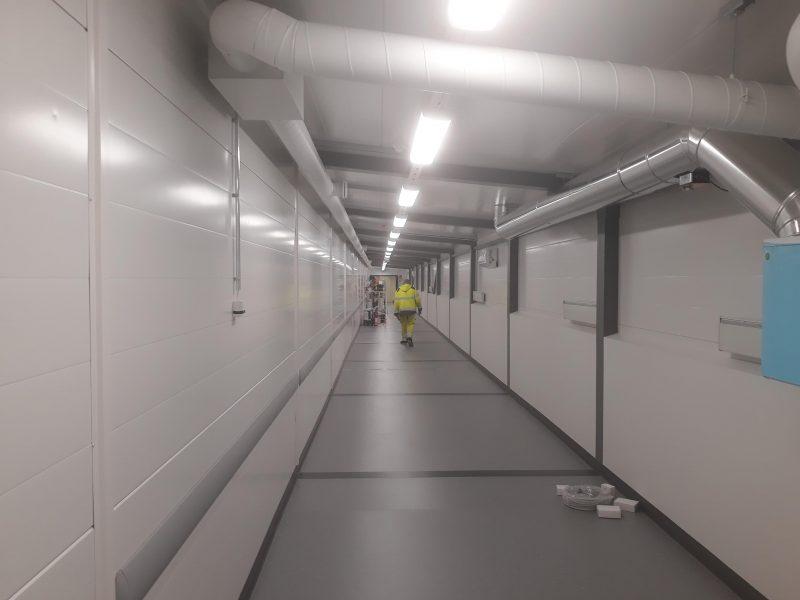 Pitkä käytävä, jonka perällä kävelee rakennusmies