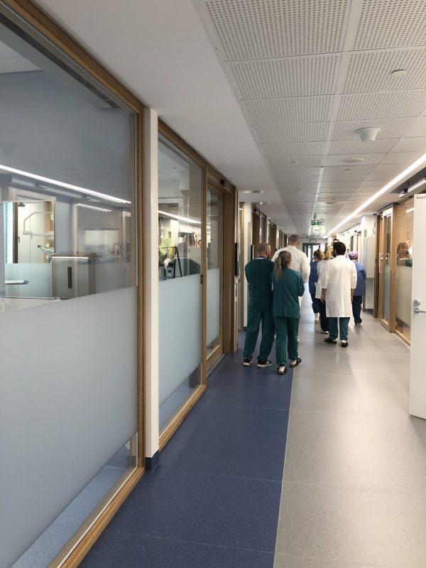 Pitkä sairaalan käytävä, jonka lopussa joukko ihmisiä kävelemässä.