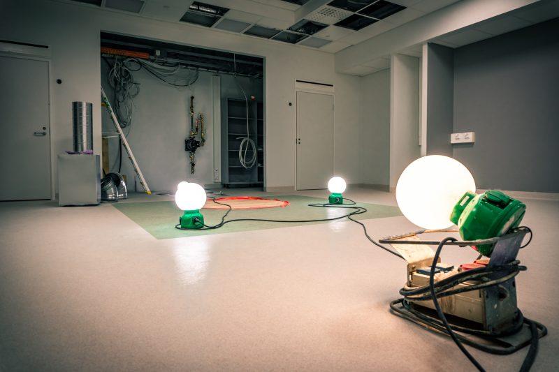 Keskeneräinen iso huone. Lattialla kolme pyöreää valaisinta johtoineen.