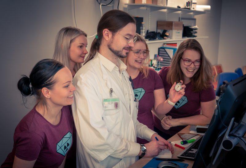 Viisi työntekijää hymyilevinä ja katosmassa samaa tietokoneruutua.