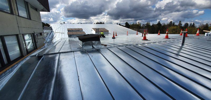 Sädehoitoyksikön suuri katto, taustalla vahvasti erottuvat pilvet.