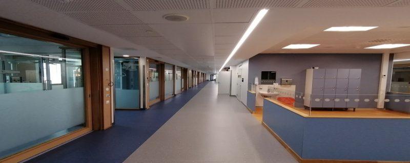 Pitkä ja leveä käytävä, jonka varrella lasiseinällisiä huoneita.