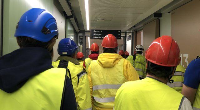Työntekijöitä turvaliiveissä ja kypärät päässä sisälllä pitkällä käytävällä.