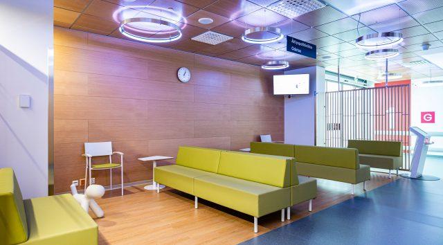 Äitiyspoliklinikan tyhjä odotustila, jossa pitkiä sohvia ja puuverhoiltu seinä.