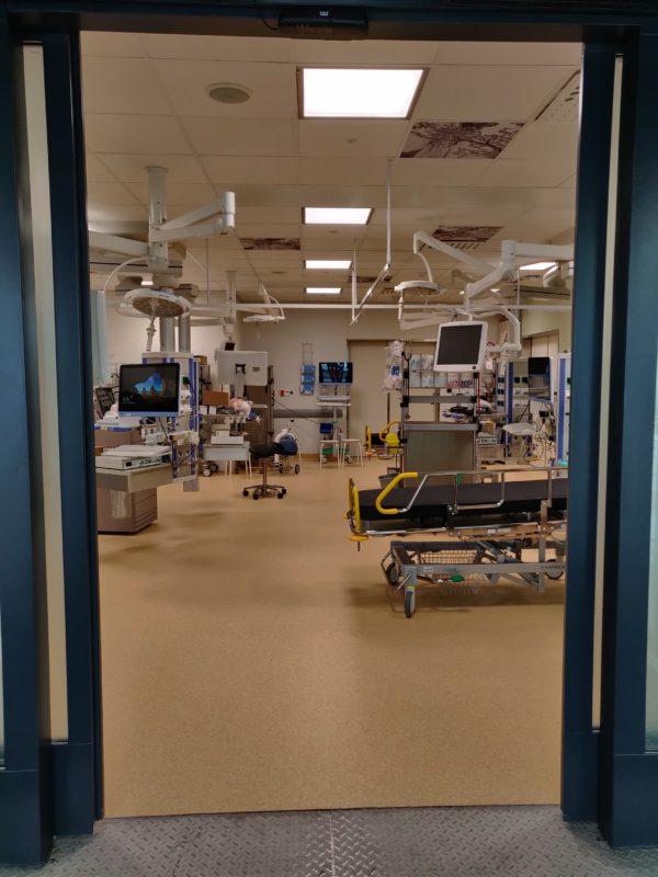 Huoneesa, potilassänkyjä ja useita katosta roikkuvia monitoreita.