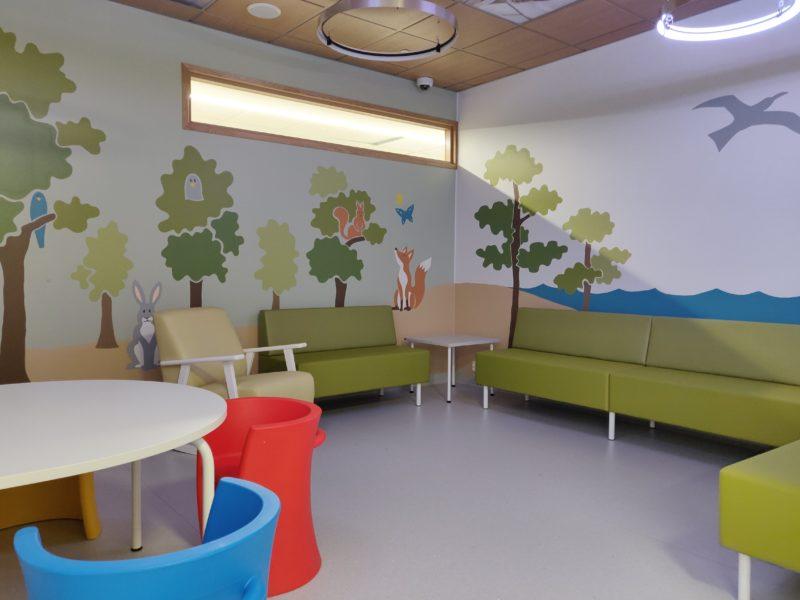 Huone, jonka seinille maalattu puita ja eläimiä., värikkäitä huonekaluja.