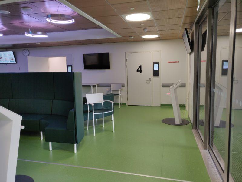 Odotusalua, jossa ilmoittautumisautomaatti ja pitkä sohva.