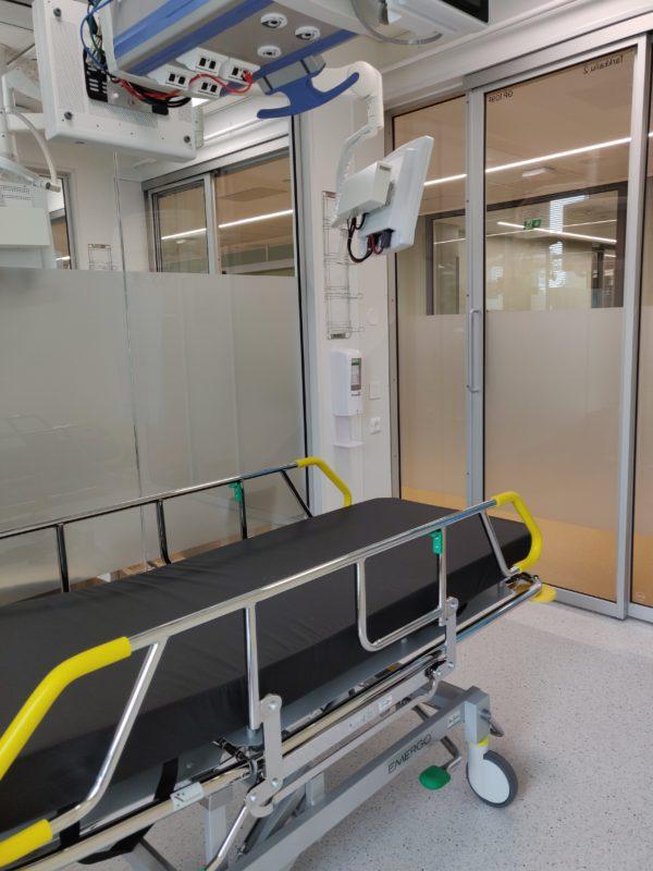 Lasiseinäinen huone, jossa potilassänky.