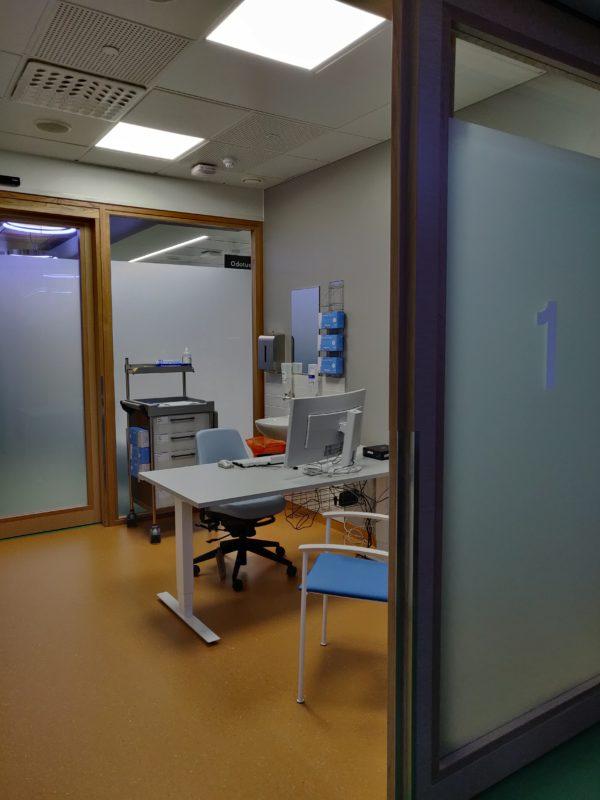 Huone, jossa vastaanottopöytä, jonka molemmin puolin tuolit.