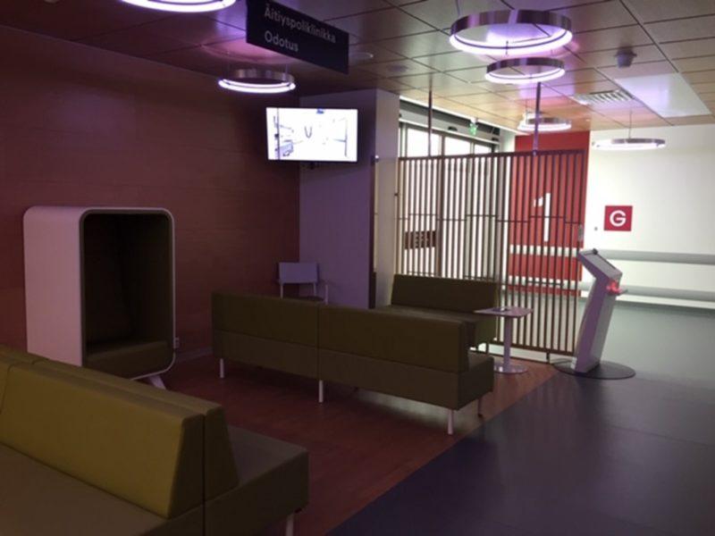 Tyhjässä aulatilassa sohvia ja ilmoittautumisautomaatti, seinässä kiinni monitori.