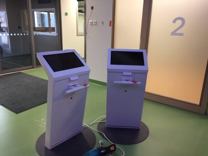 Kaksi ilmoittautumisautomaattia keskellä aulaa, johdot vielä roikkuvat irti.