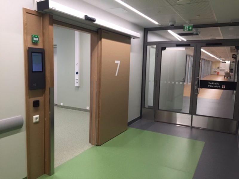 Aulatilasta avoin ovi, jossa numero 7. Oven vieressä pieni näyttö.
