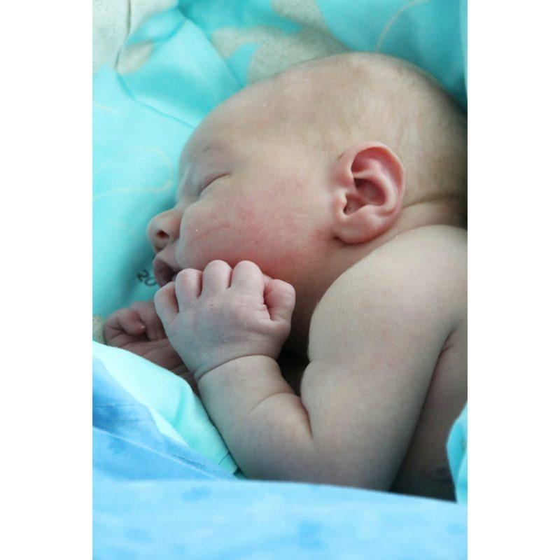 Vastasyntynyt kaljupäinen vauva lähikuvassa.