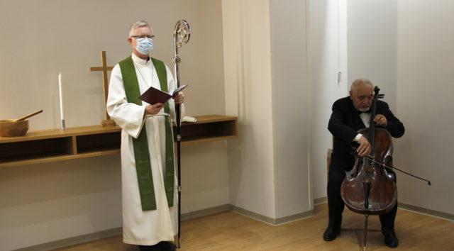Piispalla on maski kasvoillaan,, käsissään Raamattu ja sauva. Vierellä istuu mies soittamassa selloa tumma puku päällään.
