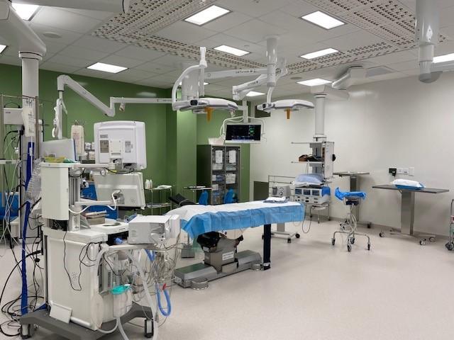Leikkaussali, jossa leikkauspaikka ja kattoon kiinnitettyjä monitoreita