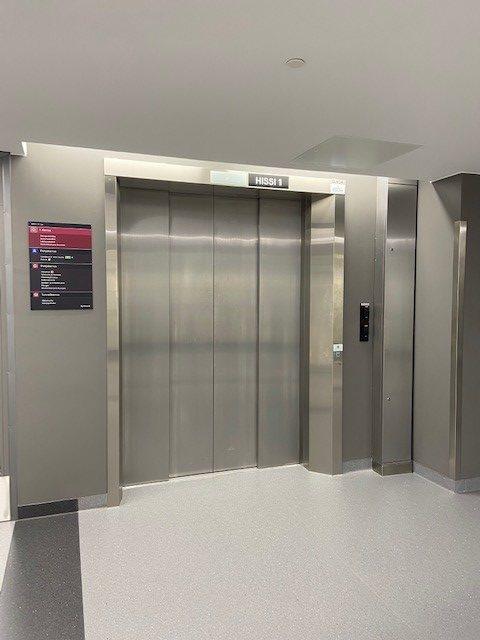 Suuri metallinen hissi tyhjässä aulassa